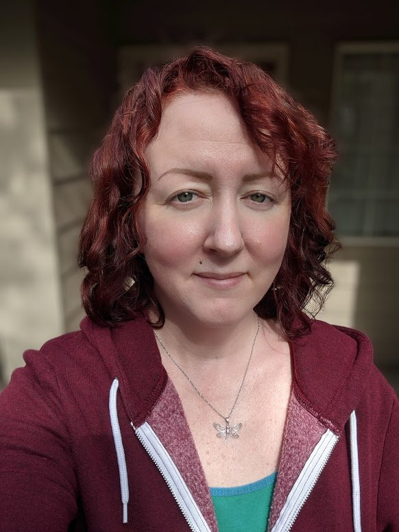 a photo of a person with red hair, green eyes, wearing a silver dragonfly necklace and a burgundy hoody