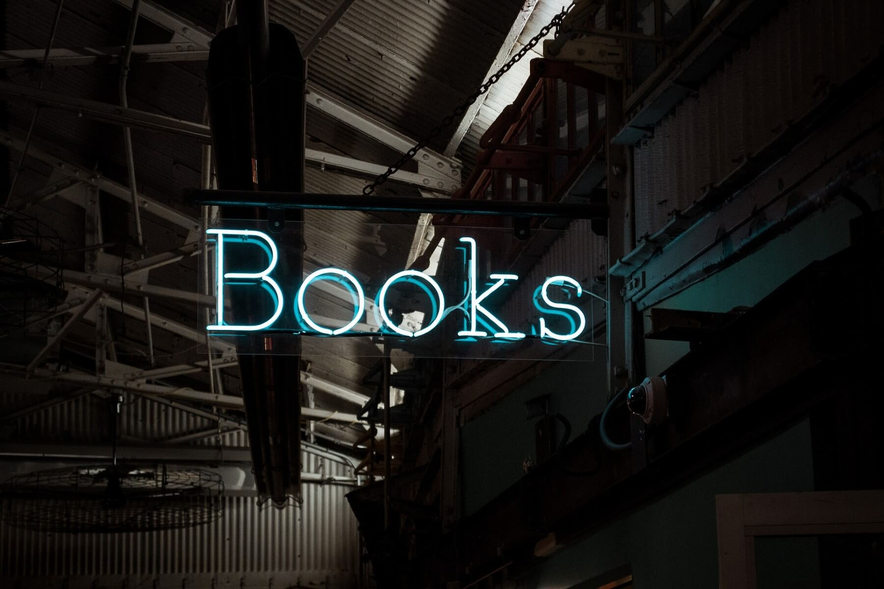 a blue neon sign that says books hanging near an open industrial ceiling