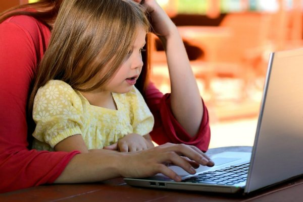 child at a computer with adult