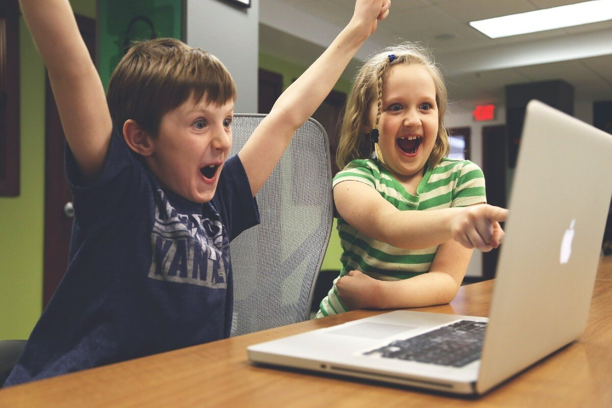 two children cheering and excited, pointing at computer screen