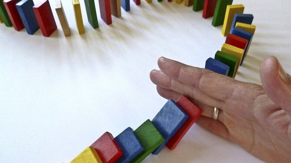 a hand in a row of dominos stopping the effect of pushing one over