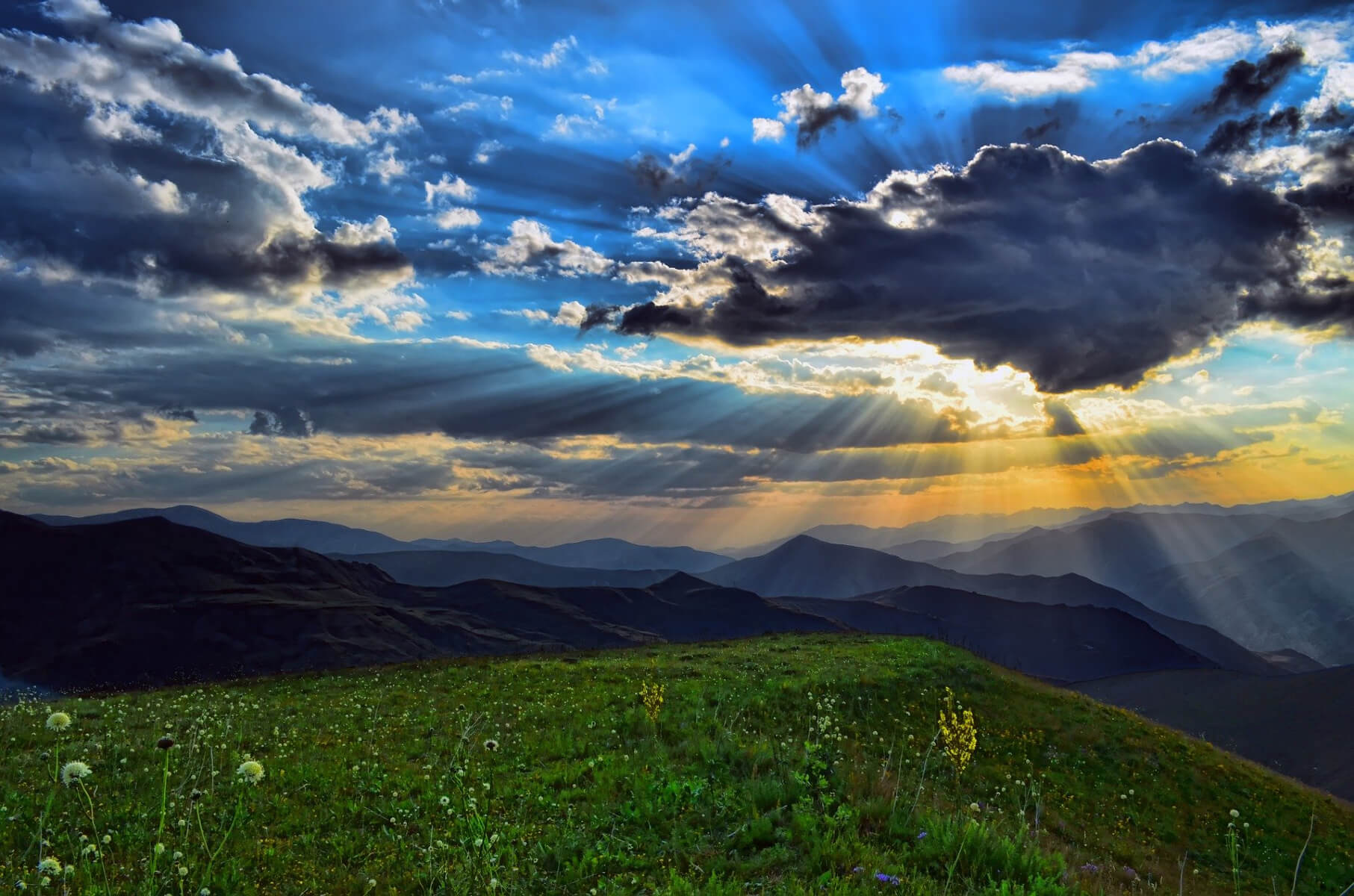 sun beams shining down through clouds on lush landscape of grass with mountains in the back