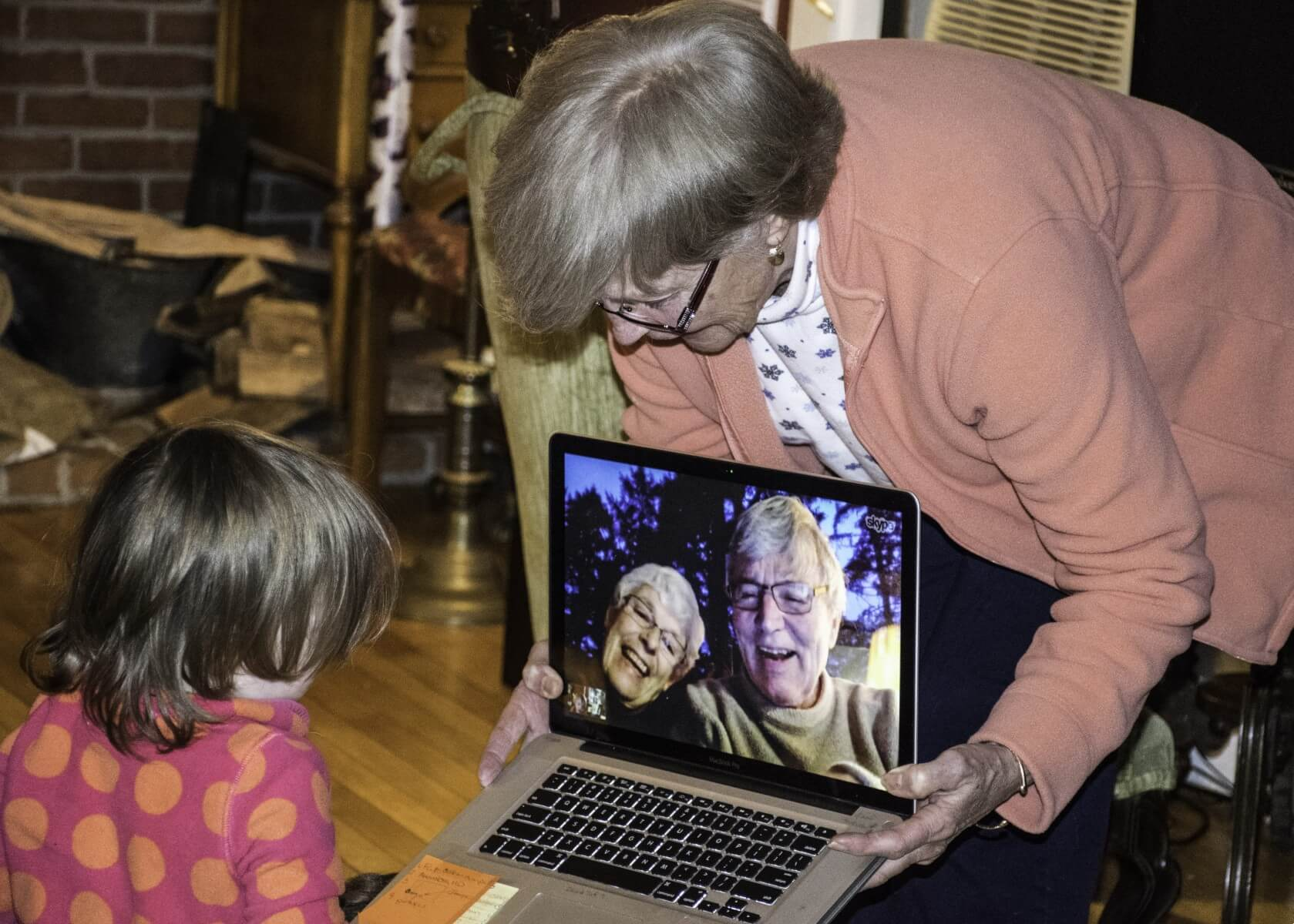 an adult holding a laptop for a child. On the screen are two smiling people in video chat.