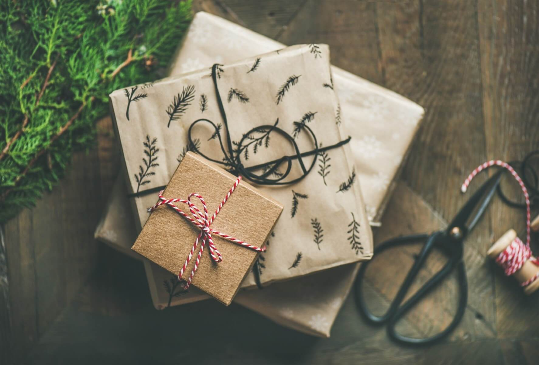 three wrapped gifts with scissors and string next to them